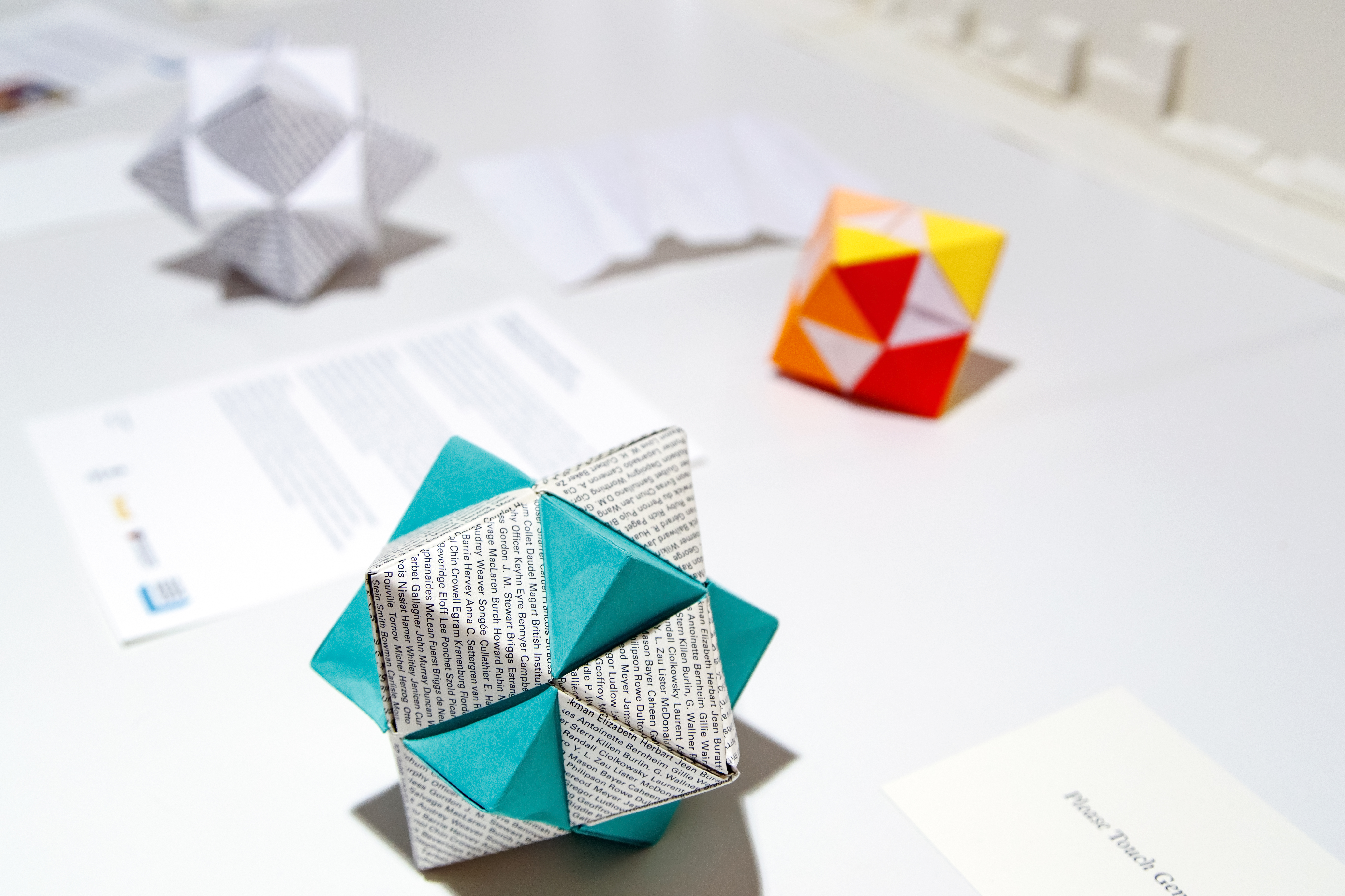 Folded origami model of a green cube intersecting a white octahedron covered with printed text.